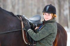 Młoda kobieta przystosowywa pocięgle przed jeździeckim koniem Obrazy Stock