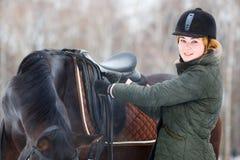 Młoda kobieta przystosowywa pocięgle przed jeździeckim koniem Zdjęcia Royalty Free
