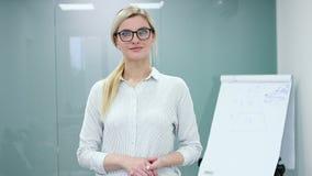 MÅ'oda kobieta psycholog przygotowywa nagrywać jej prezentacjÄ™ z flipchart przed kamerÄ… zdjęcie wideo