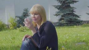 Młoda kobieta relaksuje na koc w parku cieszy się jej napój zbiory