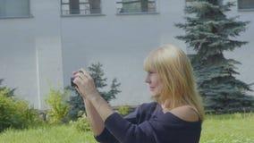 Młoda kobieta relaksuje na koc w parku i fotografuje naturę wokoło ona zbiory