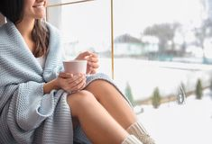 Młoda kobieta relaksuje podczas gdy pijący herbacianego pobliskiego okno zdjęcia royalty free
