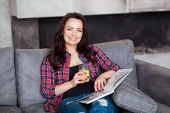 Młoda Kobieta Relaksuje w domu z szkłem sok pomarańczowy Piękna dziewczyna w przypadkowym stylu siedzi na kanapie i czyta a Zdjęcie Stock