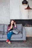 Młoda Kobieta Relaksuje w domu z szkłem sok pomarańczowy Piękna dziewczyna w przypadkowym stylu siedzi na kanapie i czyta a Zdjęcie Royalty Free