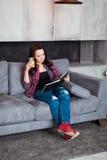 Młoda Kobieta Relaksuje w domu z szkłem sok pomarańczowy Piękna dziewczyna w przypadkowym stylu siedzi na kanapie i czyta a Obrazy Stock