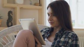 Młoda kobieta relaksuje z brown włosy texting na jej pastylce, ono uśmiecha się, zdjęcie wideo