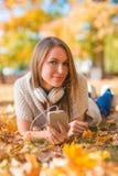 Młoda kobieta relaksuje z jej muzyką w parku Fotografia Royalty Free