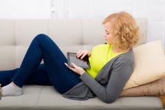 Młoda kobieta relaksuje z pastylka pecetem na kanapie zdjęcia stock