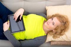 Młoda kobieta relaksuje z pastylka pecetem na kanapie obraz royalty free