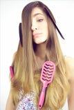 Młoda kobieta robi śmiesznej twarzy z muśnięciami i gręplą wtykać w włosy Fotografia Stock