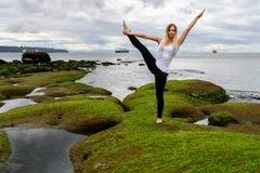 Młoda kobieta robi akrobatycznym ćwiczeniom przy intertidal strefą obrazy stock