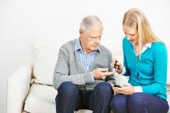 Młoda kobieta robi badaniu krwi dla starszego mężczyzna zdjęcia royalty free