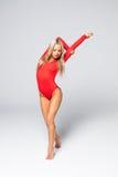 Młoda kobieta robi gimnastycznym ćwiczeniom odizolowywającym na bielu Fotografia Stock