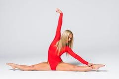 Młoda kobieta robi gimnastycznym ćwiczeniom odizolowywającym na bielu Zdjęcie Royalty Free