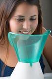 Młoda kobieta robi inhalaci z medyczną odparowalnika nebulizer maszyną na popielatym tle zdjęcie royalty free