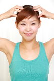 Młoda kobieta robi jaźni głowy masażowi Zdjęcia Stock
