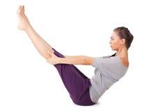 Młoda kobieta robi joga ćwiczenie Folującej Łódkowatej pozie Obrazy Royalty Free
