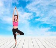 Młoda kobieta robi joga ćwiczeniu na drewnianej podłoga Fotografia Royalty Free