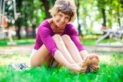 Młoda kobieta robi masażowi po treningu w parku Sport, medi obraz stock