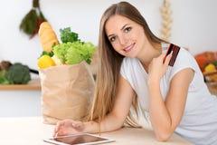 Młoda kobieta robi online zakupy pastylka komputerem i kredytową kartą Gospodyni domowa zakłada nowego przepis dla gotować w a zdjęcia stock