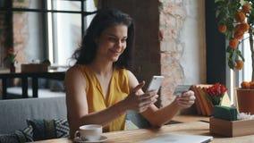 Młoda kobieta robi online zapłacie z smartphone w cukiernianej mienie banka karcie zbiory