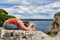 Młoda kobieta robi powikłanemu joga ćwiczeniu na skale nad piękna rzeka Zdjęcia Royalty Free
