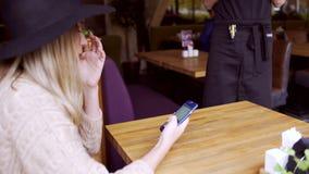 Młoda kobieta robi rozkazowi w kawiarni zbiory