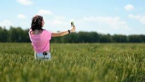 Młoda kobieta robi selfies w zielonym pszenicznym polu zbiory