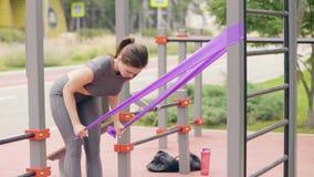 Młoda kobieta robi sprawności fizycznej ćwiczeniu z sporta expander na sportach gruntuje zbiory