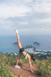 Młoda kobieta robi stojący rozszczepionego joga ćwiczenie na halnym szczycie przeciw chmurnemu niebu, morzu i wyspom w tle, napad fotografia stock