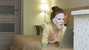 Młoda kobieta robi twarzowej maski masce z czyścić maskę, pracuje za laptopem w domu Zdjęcia Stock