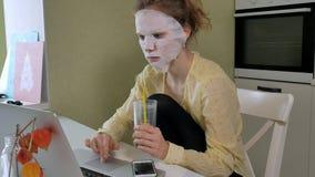 Młoda kobieta robi twarzowej maski masce z czyścić maskę, pracuje za laptopem w domu Obrazy Royalty Free
