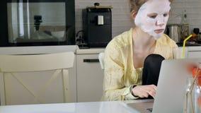 Młoda kobieta robi twarzowej maski masce z czyścić maskę, pracuje za laptopem w domu Obrazy Stock