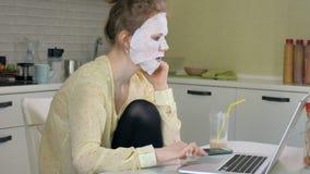 Młoda kobieta robi twarzowej maski masce z czyścić maskę, pracuje za laptopem w domu Zdjęcie Stock