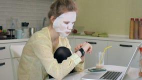Młoda kobieta robi twarzowej maski masce z czyścić maskę, pracuje za laptopem w domu Zdjęcia Royalty Free