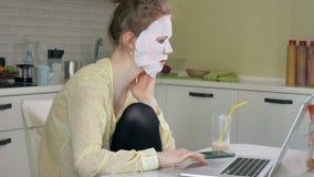 Młoda kobieta robi twarzowej maski masce z czyścić maskę, pracuje za laptopem w domu Fotografia Royalty Free