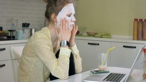 Młoda kobieta robi twarzowej maski masce z czyścić maskę, pracuje za laptopem w domu Zdjęcie Royalty Free