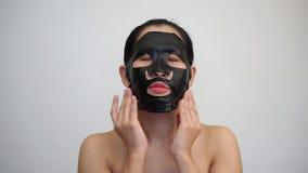 Młoda kobieta robi twarzowemu czerni maski prześcieradłu z purifying maską dalej zbiory wideo