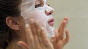 Młoda kobieta robi twarzowemu maski prześcieradłu z purifying maską na jej twarzy zbiory