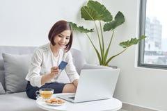 Młoda kobieta robi zakupy online z kredytową kartą i laptopem w domu fotografia stock