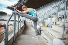 Młoda kobieta rozciąga outdoors i robi grże up ćwiczy Stażowy i pracujący sportsmenki pojęcie out fotografia stock