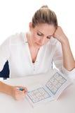 Młoda Kobieta Rozwiązuje Sudoku Fotografia Stock