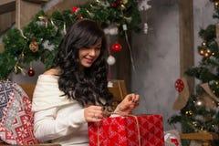 Młoda kobieta rozwija się prezent blisko choinki Fotografia Royalty Free