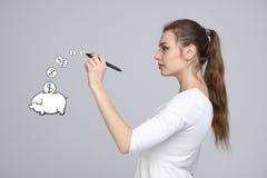 Młoda kobieta rysuje prosiątko banka Zdjęcie Stock
