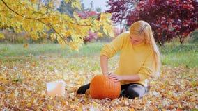 Młoda kobieta rzeźbi bani Siedzieć w jardzie w tle yellowing drzewa zbiory wideo