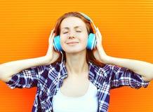 Młoda kobieta słucha dobrą muzykę w hełmofonach i cieszy się zdjęcie stock
