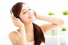 Młoda kobieta słucha muzykę z hełmofonami zdjęcia stock