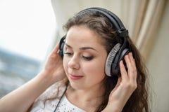 Młoda kobieta słucha muzyka na hełmofonach Fotografia Stock
