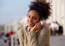 Młoda kobieta słucha muzyka na hełmofonach outdoors Zdjęcia Royalty Free