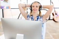 Młoda kobieta słucha muzyka podczas gdy pracujący na komputerze obrazy royalty free